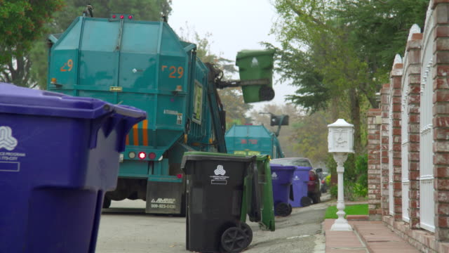 ms rear view of  garbage trucks picking up garbage bins, north hollywood, california, usa - garbage truck stock videos and b-roll footage