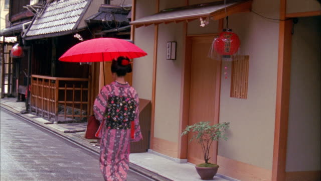 ws rear view of geisha with red umbrella walking down narrow street in gion area, kyoto, japan - kimono stock videos & royalty-free footage