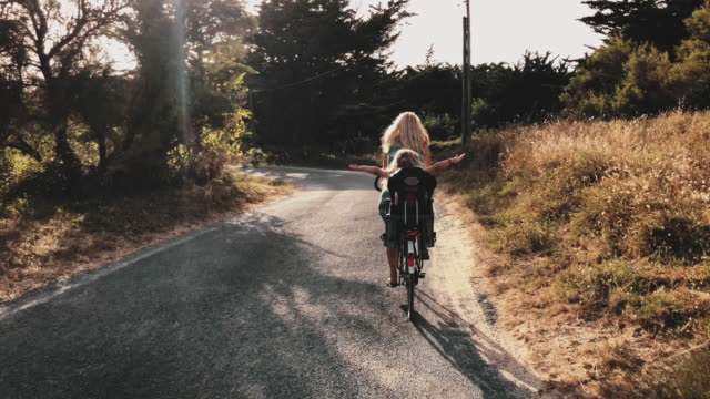 vídeos y material grabado en eventos de stock de vista trasera de chica disfrutando de paseo en bicicleta con mujer - soleado