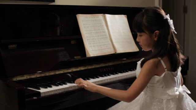 MS Rear view of girl wearing white dress, playing piano / China