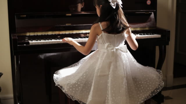 MS Rear view of girl wearing white dress, playing piano then looking at camera / China
