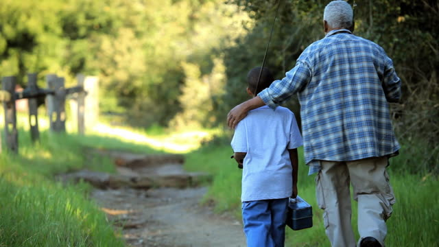 ms rear view of grandfather and grandson (8-9) walking on field with fishing poles on their shoulders / los angeles, california, usa - grandparent stock videos & royalty-free footage