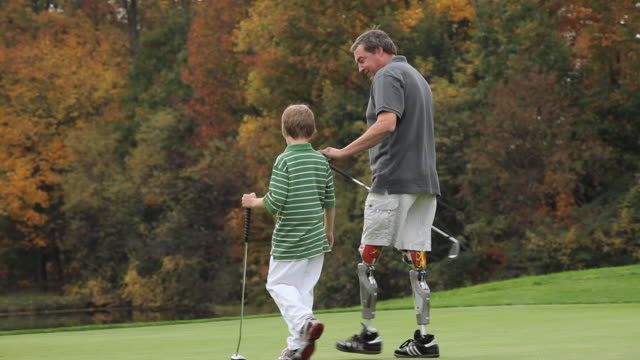 vídeos y material grabado en eventos de stock de ws pan rear view of grandfather with two prosthetic legs and grandson (8-9) walking on golf course / richmond, virginia, usa - equipo protésico
