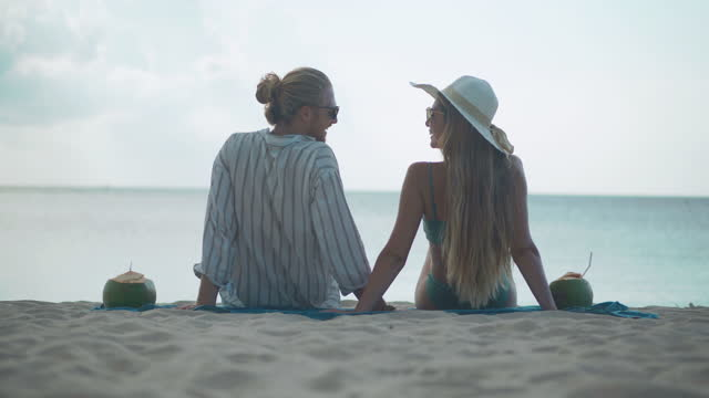 rear view of happiness to couples of latin american and hispanic ethnicity and she wearing white bonnet hat,sitting with romance along edge of sunset sea on sand beach. happy family holidays.non-caucasian honeymoon concept - wonderlust stock videos & royalty-free footage