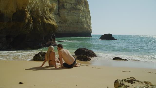 rear view of happy couple sitting on beach relaxing in ocean waves / caroviero, faro, portugal - badbyxor bildbanksvideor och videomaterial från bakom kulisserna