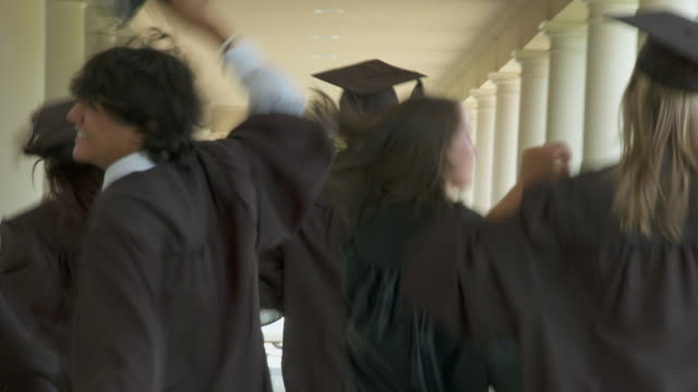 ms, pov, defocus, rear view of high school graduates running along school walkway, richmond, virginia, usa - mortarboard stock videos and b-roll footage