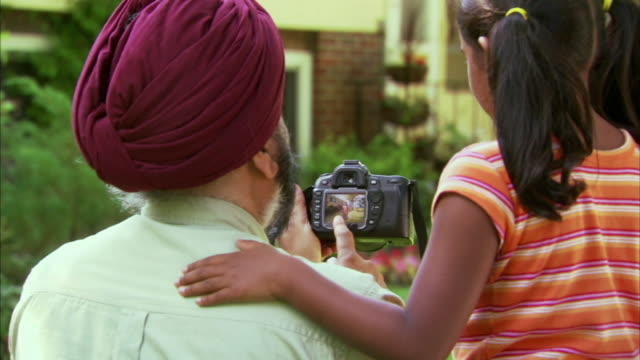 cu rear view of indian man with granddaughter (6-7) looking at picture in digital camera in garden, halifax, nova scotia, canada - see other clips from this shoot 1464 stock videos and b-roll footage