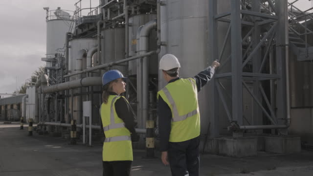 rear view of industrial workers inspecting industrial plant wearing protective workwear and pointing up - health and safety stock videos & royalty-free footage