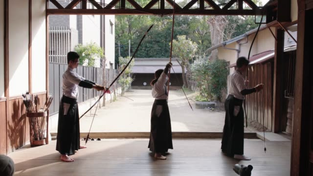 rear view of japanese archers practicing in their dojo - japanese culture stock videos & royalty-free footage