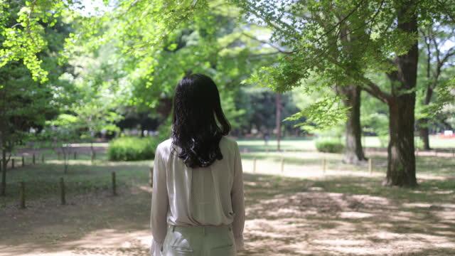 vídeos y material grabado en eventos de stock de vista trasera de la mujer japonesa caminando en el parque público, bajo hojas verdes frescas - vista posterior