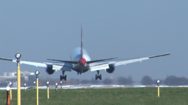 rear view of jet landing at heathrow with no clearly noticeable view of livery or branding eventually turns at end of clip after landing to show... - back stock videos & royalty-free footage