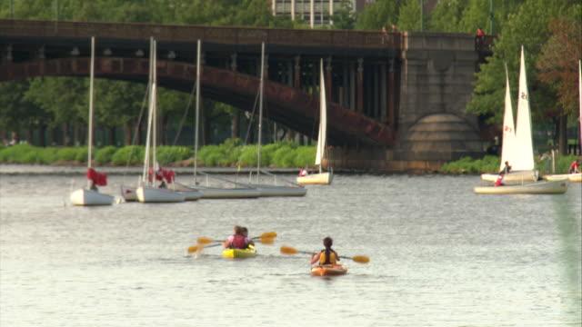 WS Rear view of kayakers paddling through toward Longfellow Bridge, small sailboats in background / Boston, Massachusetts, USA