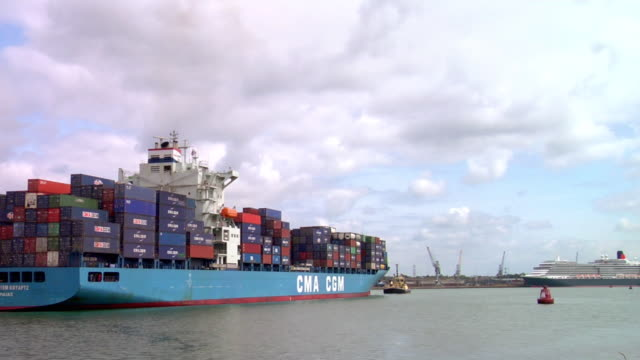 stockvideo's en b-roll-footage met ws rear view of large cargo ship being towed through harbor, hampshire, united kingdom - southampton engeland