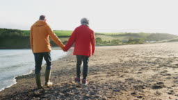 Rear view of loving senior couple holding hands walking along shoreline on winter beach vacation - shot in slow motion