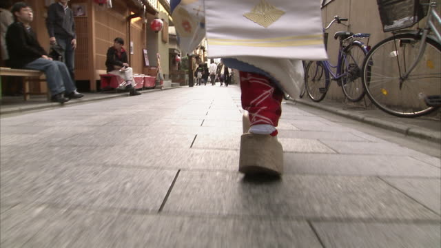 cu ds rear view of maiko's feet walking down narrow street, kyoto, japan - アシ点の映像素材/bロール
