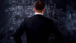 Rear view of man against chalkboard with math formula equations