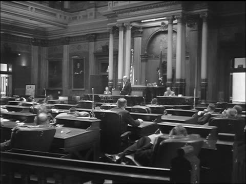 b/w 1957 rear view of man at podium addressing smoking men in michigan state legislature / lansing - lansing stock videos & royalty-free footage