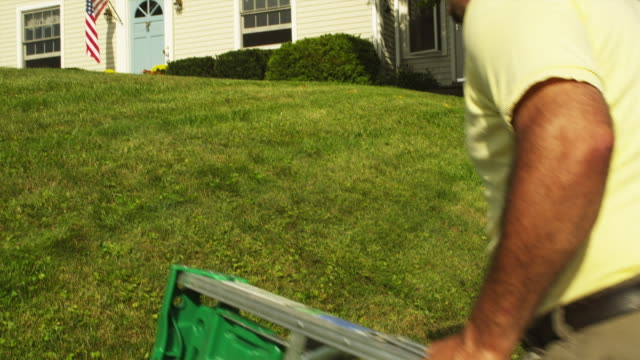 ms tu rear view of man carrying step ladder to front of home, manchester, vermont, usa - step ladder stock videos & royalty-free footage