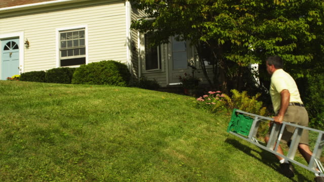 ws pan rear view of man carrying step ladder to front of home, manchester, vermont, usa - step ladder stock videos & royalty-free footage