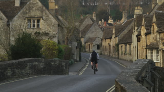 ws rear view of man cycling on road crossing old stone village, castle combe, united kingdom - wiltshire stock videos & royalty-free footage