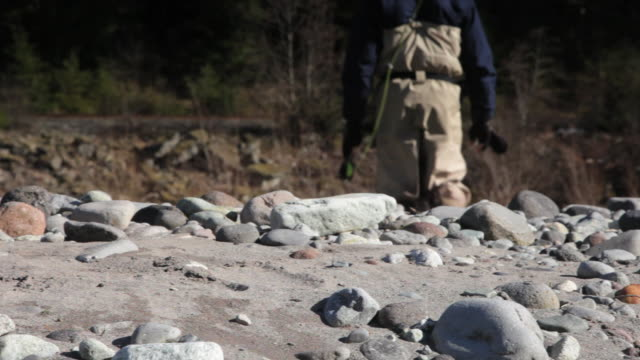 cu pan selective focus rear view of man fishing in cheakamus river, pebbles in foreground, squamish, british columbia, canada - squamish stock videos & royalty-free footage