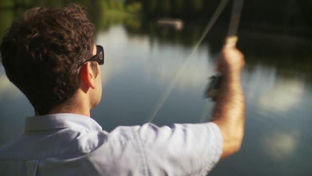 cu rear view of man fly fishing in forest lake, morristown, vermont, usa - korta ärmar bildbanksvideor och videomaterial från bakom kulisserna