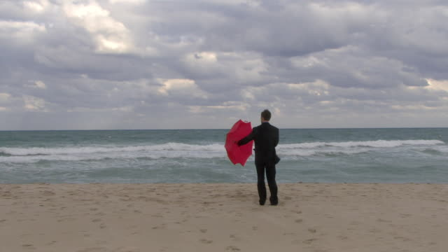 ws rear view of man in full suit opening umbrella on beach / miami, florida, usa - full suit stock videos and b-roll footage