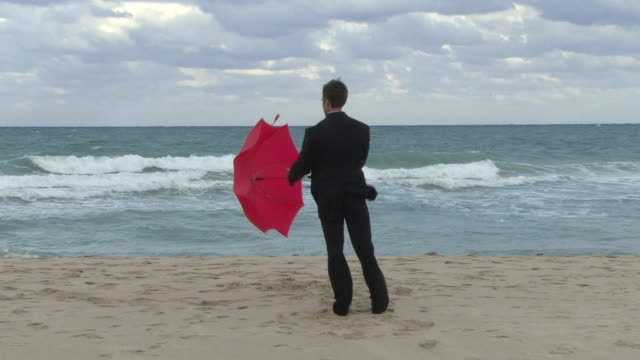 ws rear view of man in full suit opening umbrella on beach / miami, florida, usa - full suit stock videos & royalty-free footage