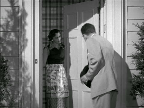 b/w 1952? rear view of man meeting couple at door of home / they let him in - stereotypical housewife stock videos and b-roll footage