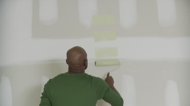 CU, Rear view of man painting wall with paint roller, Plainfield, New Jersey, USA