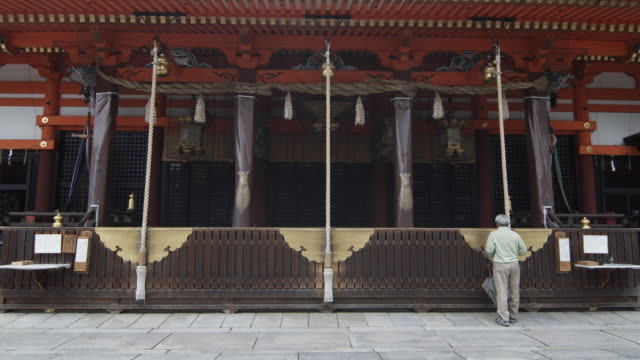ms rear view of man praying in front of yasaka shrine, gion, kyoto, japan - shrine stock videos & royalty-free footage