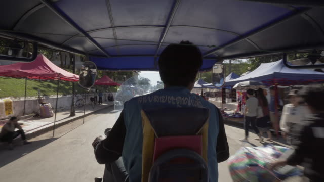 rear view of man riding motorcycle taxi on street amidst market stalls in city during sunny day - luang phabang, laos - off the beaten path stock videos & royalty-free footage