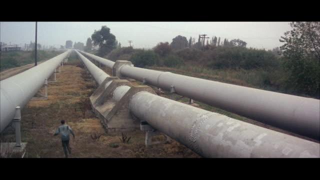 vídeos y material grabado en eventos de stock de 1967 ws rear view of man running through field between big pipelines - escapar