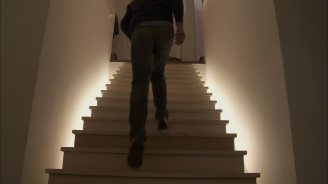 WS LA Rear view of man running upstairs / Brussels, Belgium
