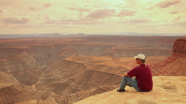 stockvideo's en b-roll-footage met ws rear view of man sitting on edge of canyon enjoying views / muley point, utah, usa - baseballpet