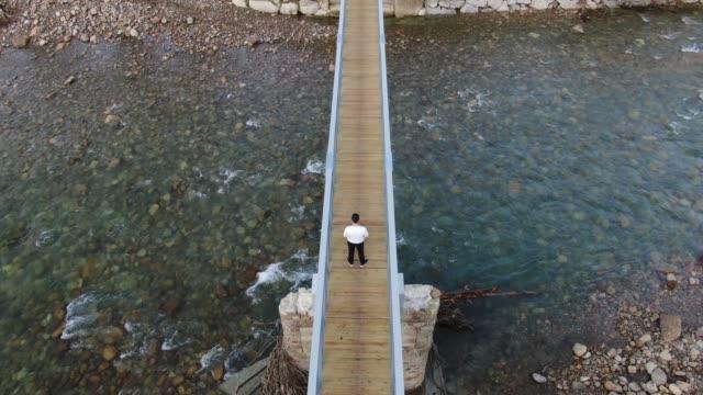 vídeos de stock e filmes b-roll de rear view of man standing on a wooden pedestrian bridge over a river - cruzar