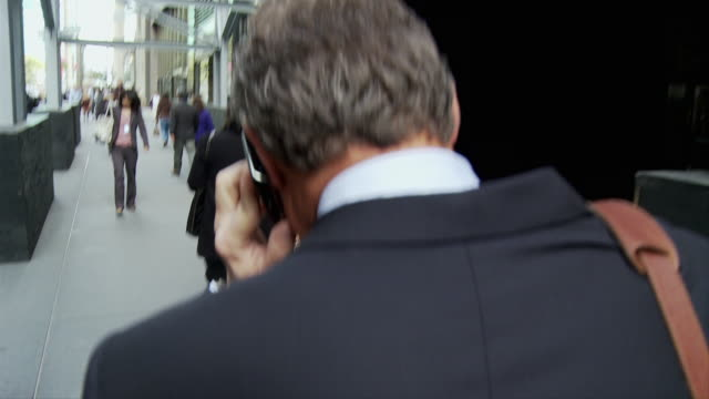 vídeos de stock e filmes b-roll de cu rear view of man talking on smart phone on street / new york city, new york, usa - só homens maduros