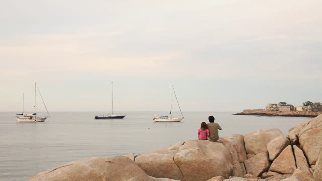 ws rear view of man with daughter (6-7) sitting on rocky beach / rockport, massachusetts, usa - rockport massachusetts stock videos & royalty-free footage