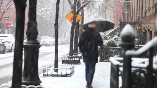 stockvideo's en b-roll-footage met ms selective focus rear view of man with umbrella walking down greenwich village street in snow / new york city, new york, usa - wit haar