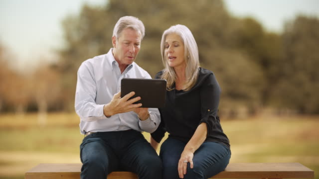 Rear view of mature couple looking at a green screen