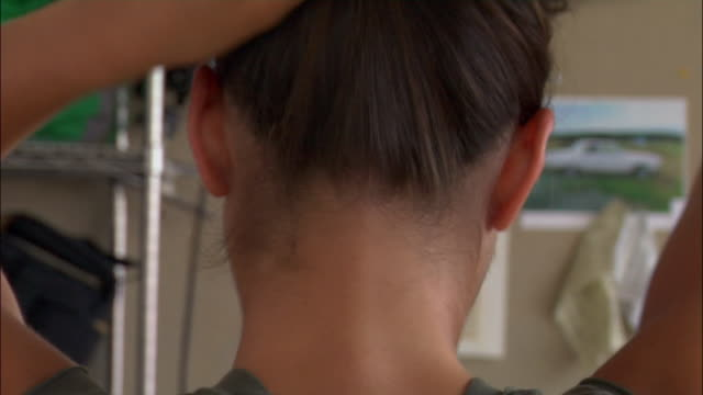 Rear view of model's hair being put up into ponytail by stylist