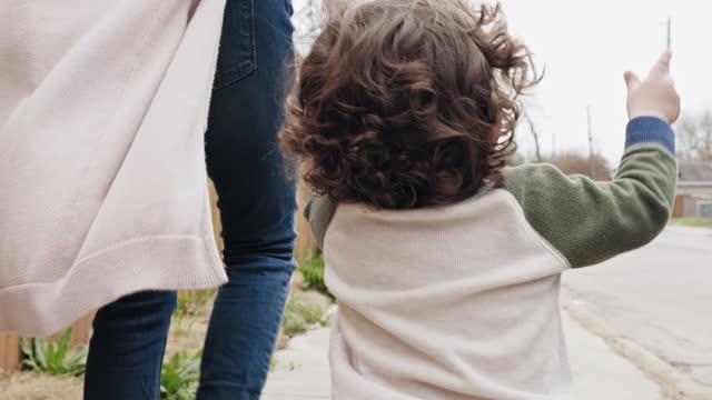 vídeos de stock, filmes e b-roll de visão traseira da mãe e do filho bebê andando de mãos dadas - gesticular