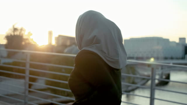 rear view of muslim woman in hijab running in sunset (slow motion) - hijab stock videos & royalty-free footage