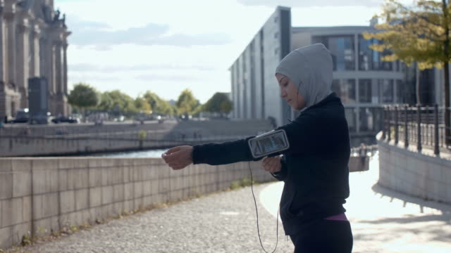 rear view of muslim woman in sport hijab putting on arm band (slow motion) - middle eastern ethnicity stock videos and b-roll footage