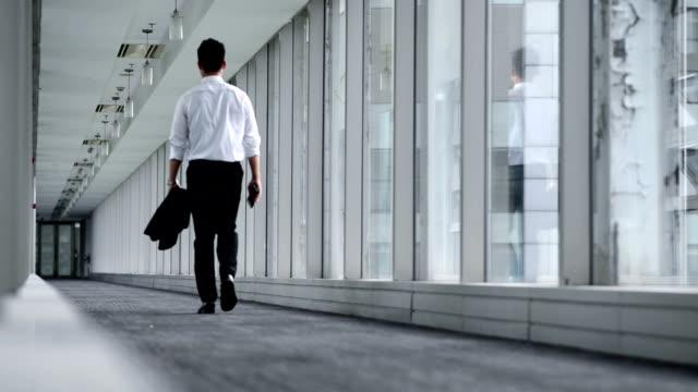 vidéos et rushes de vue arrière d'un jeune homme marchant au couloir - moquette