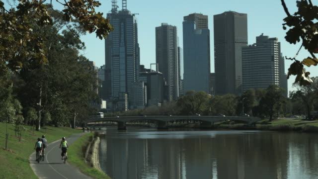 WS Rear view of people cycling on path along river, downtown skyline in background, Melbourne, Victoria, Australia