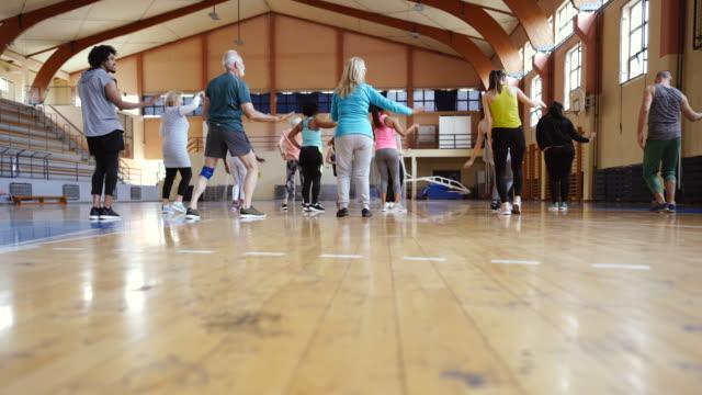 vídeos de stock, filmes e b-roll de opinião traseira a dança dos povos na classe latin do aerobics - aula de exercícios