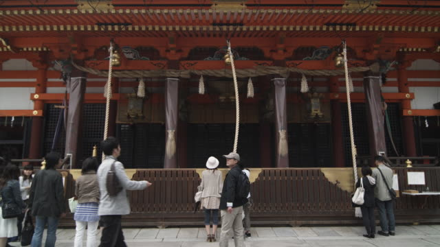 ms rear view of people donating money and praying in front of yasaka shrine, gion, kyoto, japan - shrine stock videos & royalty-free footage