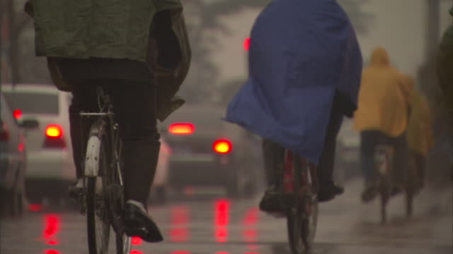 slo ms rear view of people in colorful ponchos riding bicycles along side traffic in rain, beijing, china - waterproof clothing stock videos & royalty-free footage