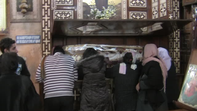 ms, rear view of people praying in front of opened coffin, monastery of saint anba bishoy, wadi el-natrun, egypt - coffin stock videos & royalty-free footage